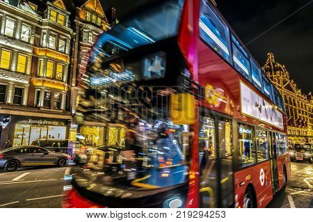 LONDON - NOVEMBER 29 2017: Night view with red double decker bus on moving in front of Harrods the biggest luxury department store from the Europe.