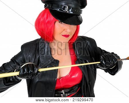 Dominant woman wearing latex and leather red and black military clothes including gloves cap and coat. In a short red wig and holding a whip. Fetish cosplay. White background. poster