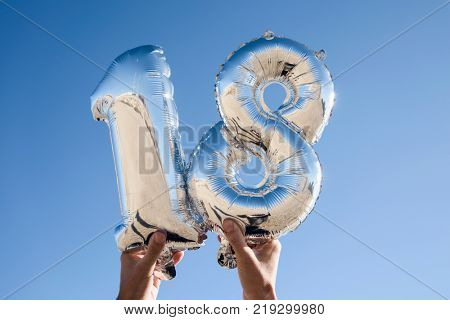 closeup of the hands of a young man holding some silvery number-shaped balloons forming the number 18 against the blue sky