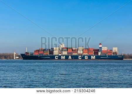 Stade, Germany - December 18, 2015: Container ship CMA CGM TANYA on Elbe river. The vessel can hold up to 9300 standard containers and is owned and operated by French shipping company CMA CGM SA.