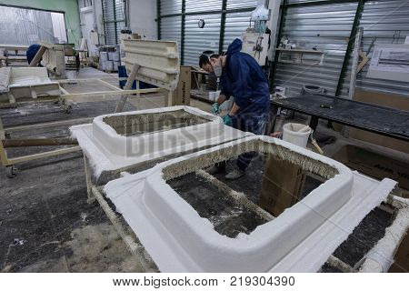 St. Petersburg Russia - June 29 2016: Painting workshop of the plant of transport engineering. Gluing and staining of facing panels of electric trains. Young mooch removes the remnants of unnecessary paint from the part