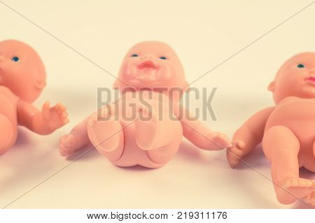 Naked Dolls, Lined Up In A Row. Concepts Of Abortion And Childbirth. Toned
