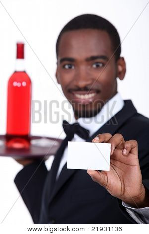 Wine waiter holding forth a business card left blank for your details