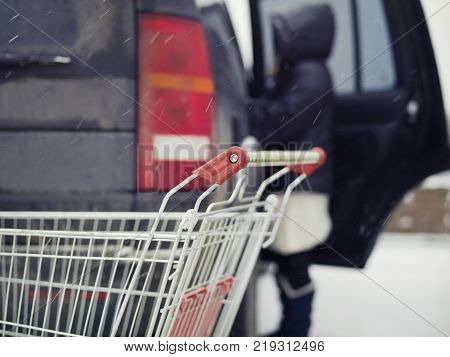 Empty shopping trolley in the foreground and woman silhouette loading goods in car. Shallow depth of field