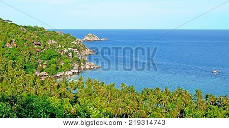 Beautiful sea scape in summer high view from moutain see many coconut trees and bungalow at coatside with big rock blue sea and white blue sky.