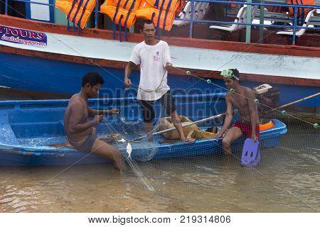 Sihanoukville Cambodia - April 29 2014: man fishing with a net in the sea in front of Sihanoukville Cambodia