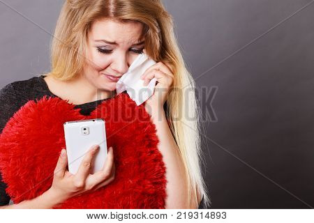 Betrayal bad relationship hurt love concept. Sad heartbroken woman crying and looking at her phone.