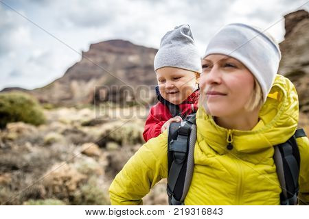 Super mom with baby boy travelling in backpack. Mother on hiking adventure with child family trip in mountains. Vacations journey with infant carried on back weekend travel in Tenerife Spain.