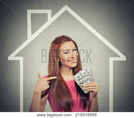 home money people concept. Smiling young successful happy business woman holding dollar cash money in hand over house and gray wall background