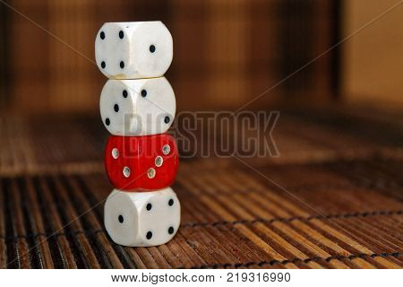 Stack of three white plastic dices and one red dice on brown wooden board background. Six sides cube with black dots. Number 1 2 3 4