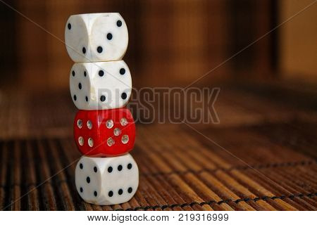 Stack of three white plastic dices and one red dice on brown wooden board background. Six sides cube with black dots. Number 3 4 5 6