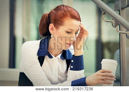 Portrait stressed sad young woman with coffee cup sitting outdoors. City urban life style stress