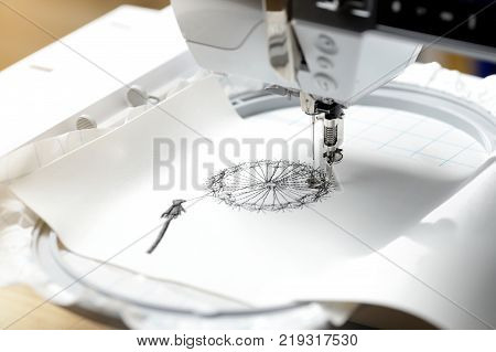embroidery with embroidery machine - dandilon on white leatherette - view on embroidery process machine head and hoop in bright sunny light mood from right