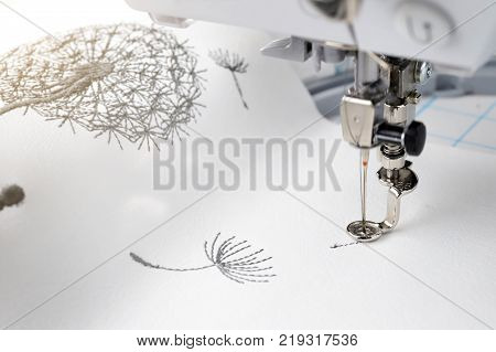 embroidery with embroidery machine - dandilon on white leatherette - bright sunny view on embroidery process with needle down machine head motif and hoop