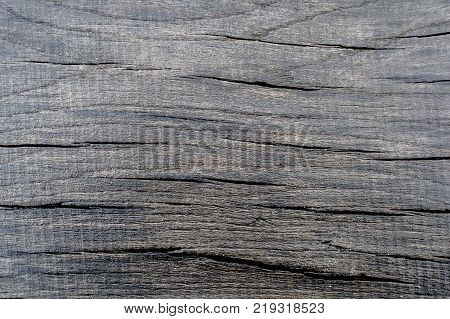 Photo of a texture of a black wet cracked wood