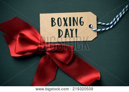 closeup of a red satin ribbon bow and the text boxing day in a brown swing tag, on a dark green background