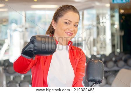 Young woman in a red sports suit wearing black boxing gloves. Boxing fitness woman smiling happy wearing boxing gloves. Portrait of sporty caucasian model in the gym.