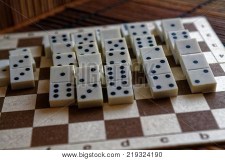 Domino pieces after domino effect on the bamboo brown wooden table background