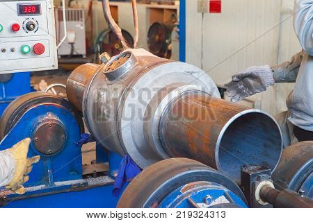 Welder worker is welding a big ball valve body by Flux-cored arc welding technology method. Ball valve is using for chemical, oil or gas industry or for power plants