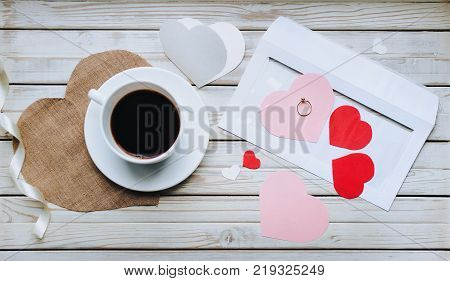A cup of coffee on the table and a ring as a gift. Proposal of marriage. Ring and confess in love. Marriage propose.
