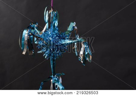 Blue pinata as decoration for Christmas and New Year on black background