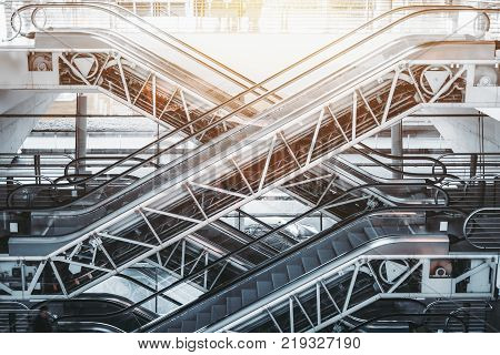 Side view of several criss-cross positioned empty modern escalators with opened internal mechanisms and gears in interior of contemporary airport terminal railway station or shopping mall on daytime