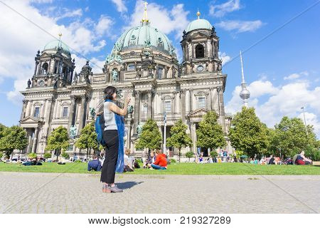 BERLIN GERMANY - AUGUST 28 2017; Young female tourist selfie taking in front baroque architecture of cathedral behind visitors and tourists enjoying warm summer day on lawn
