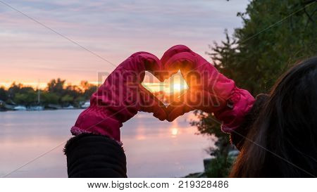 Winter solstice woman with pink gloves making heart shape with hands conceptual winter solstice, love and happiness in nature conceptual photography with room for copy, heart shape is over the water with the sunset shining through heart with trees in back