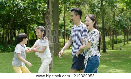 Chinese parents & kids enjoying weekend activity in park in summer