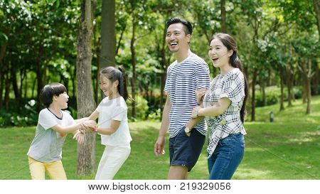 Chinese parents and kids enjoying family time in park in summer