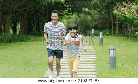 Chinese father & son smiling & running in park in summer