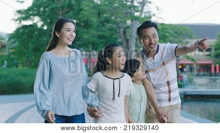 Asian family walking together on promenade excited when looking ahead