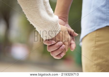 close-up of two people holding hands outdoor showing romance