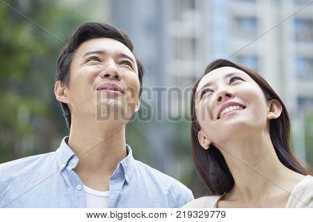 Portrait of Asian couple standing outdoor in garden, looking up & smiling