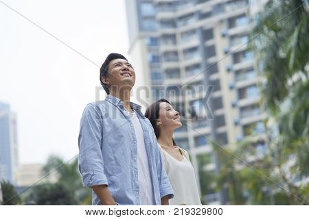 Asian couple standing outdoor in garden, looking ahead and smiling