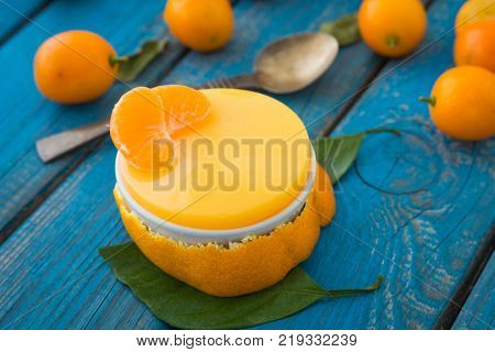 A sweet orange jelly pudding with cumquats and tangerine lobes with green leaves on blue rustic wooden background closeup