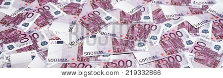 Money background consisting of purple five hundred Euro bills spread across the screen. Symbolic texture photo of wealth