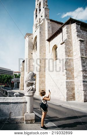 Young female tourist taking a photo on cellphone in Burgos, Spain. Traveler walking in the city and taking photo, sightseeing in Burgos