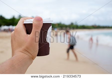 cup with coffee in hand on background of blurred tropical beach. Need to drink an invigorating coffee while on vacation