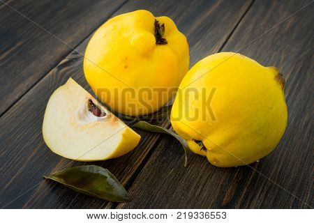 Yellow quince or queen apple autumn fruits with leaves on dark rustic wooden background closeup