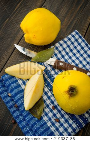 Sliced yellow quince or queen apple fruits with seeds on blue checkered towel top view