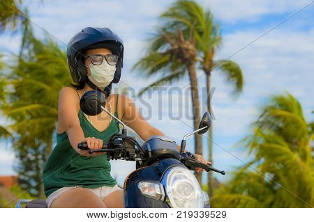 young happy and pretty Asian Chinese woman riding scooter wearing safety motorcycle helmet and protective face mask in motorbike safe ride and traffic air contamination and pollution concept