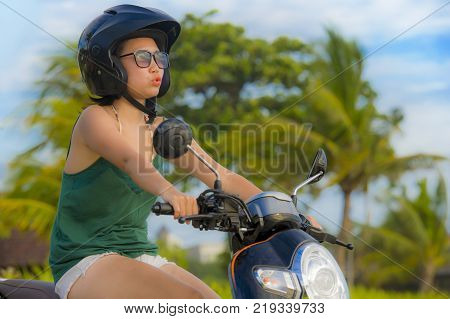 young happy and pretty Asian Chinese woman riding scooter wearing safety motorcycle helmet having fun on tropical Summer background with palm trees in motorbike safe ride and enjoying holidays concept