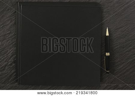 Blank Black Notebook Cover black rock table with clipping path on notebook for mockup designs