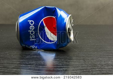 Niedomice Poland - December 22 2017: A crumpled empty Pepsi can lies on a wooden table.