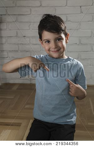 Happy boy pointing his fingers on a blank t-shirt