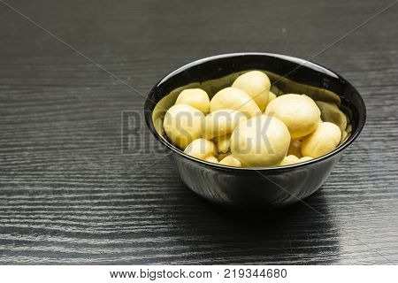Bowl with marinated mushrooms (Agaricus) on the table.