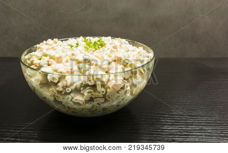 Bowl with vegetable salad on a wooden table.