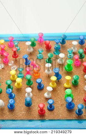 Colorful push pins stick into a cork board