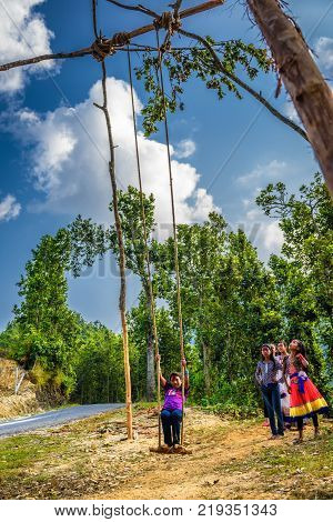 BANDIPUR, NEPAL - OCTOBER 22, 2015 : Nepalese children playing on a traditional bamboo swing called linge ping.
